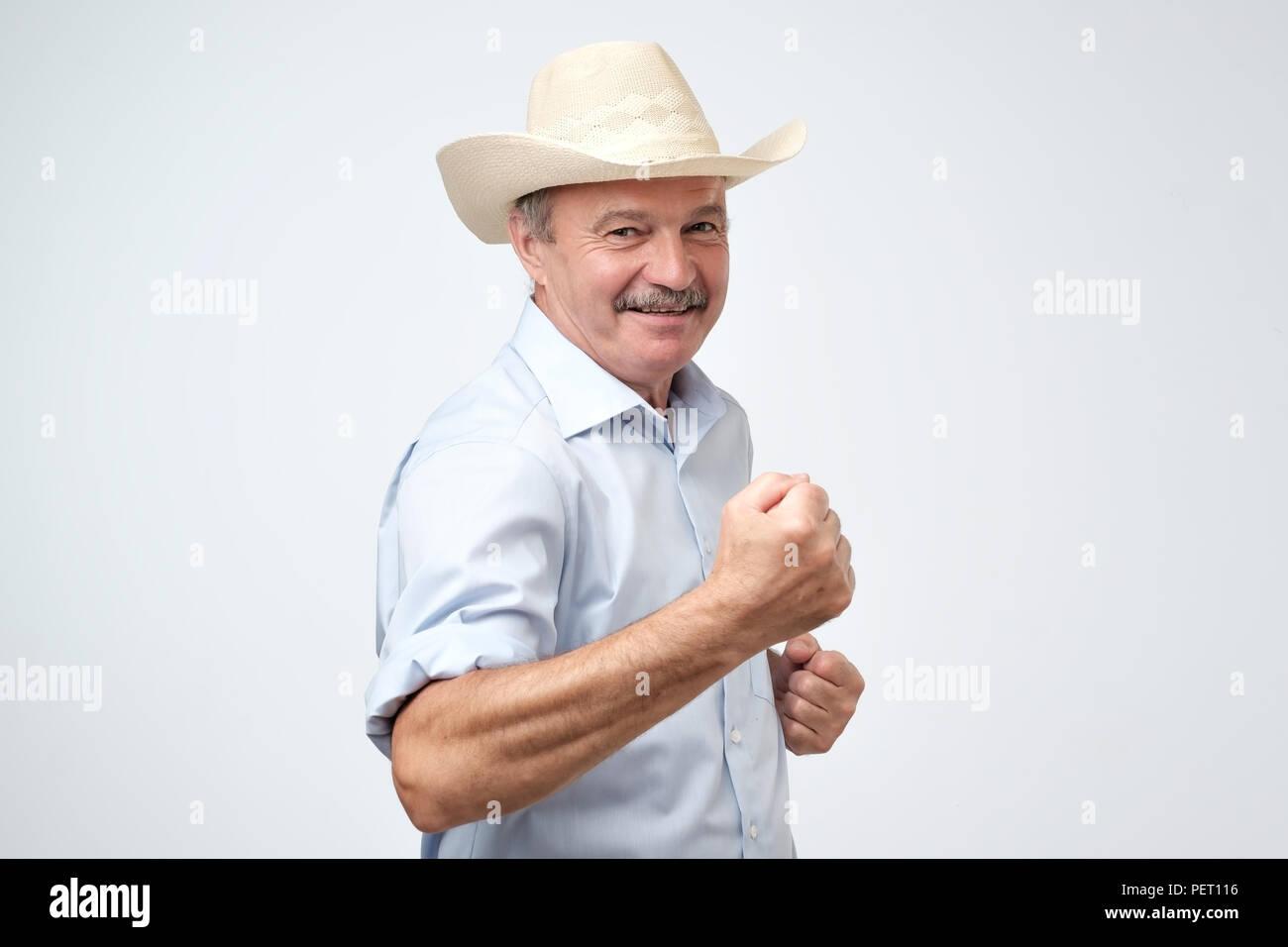 Retrato de apuesto hombre maduro exitoso llevar sombrero de cowboy celebra  su victoria sosteniendo un puño 5b2fa0bf7ce