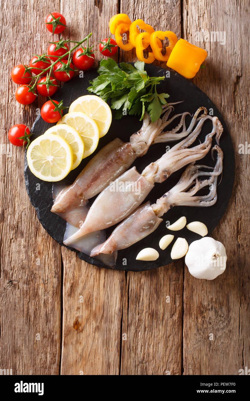 Calamares fresca cruda con tentáculos closeup y de ingredientes vegetales en la mesa. Vista superior de la vertical desde arriba Imagen De Stock