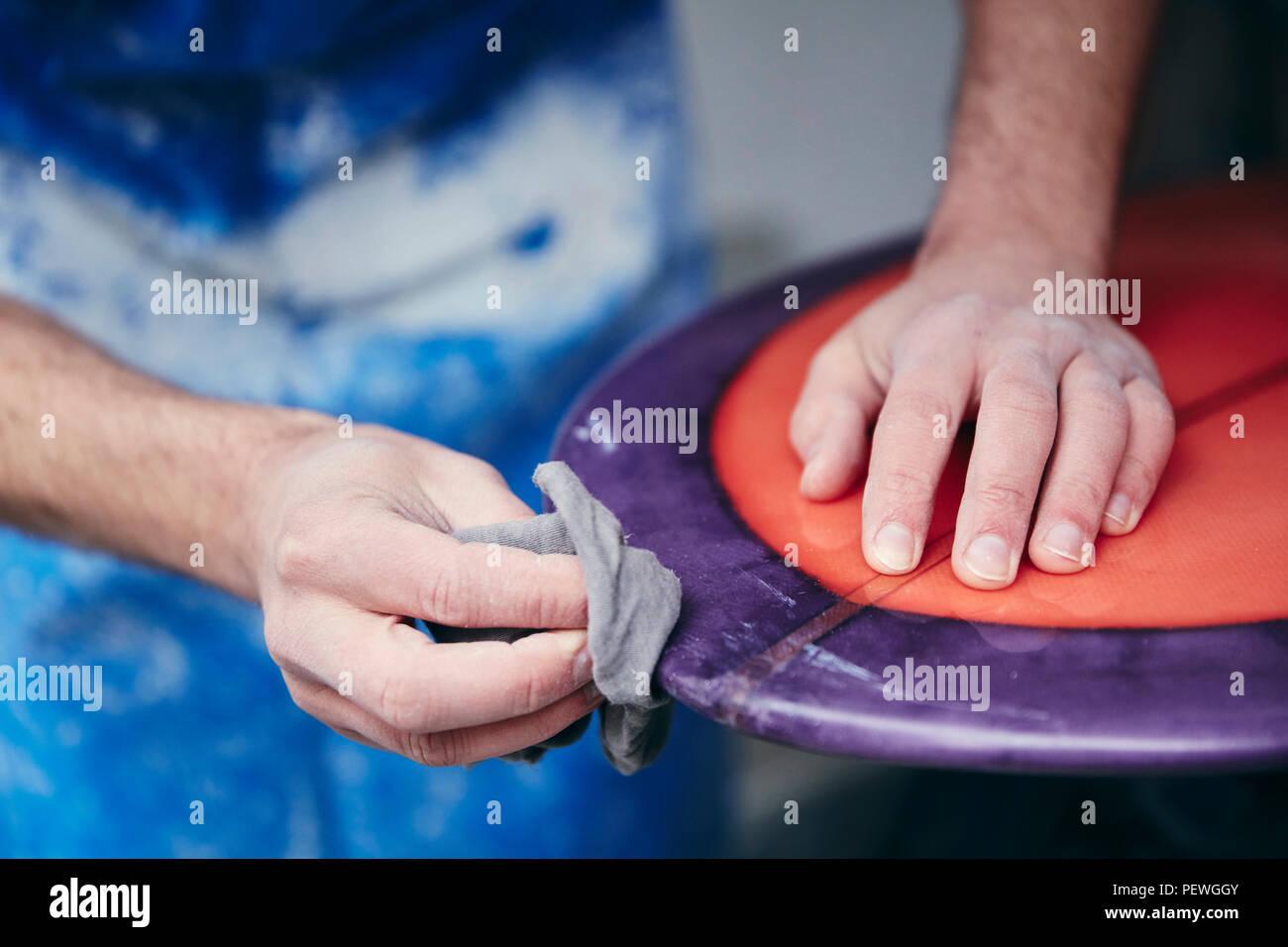 Hombre lijado y la conformación de una tabla de surf en un taller Imagen De Stock