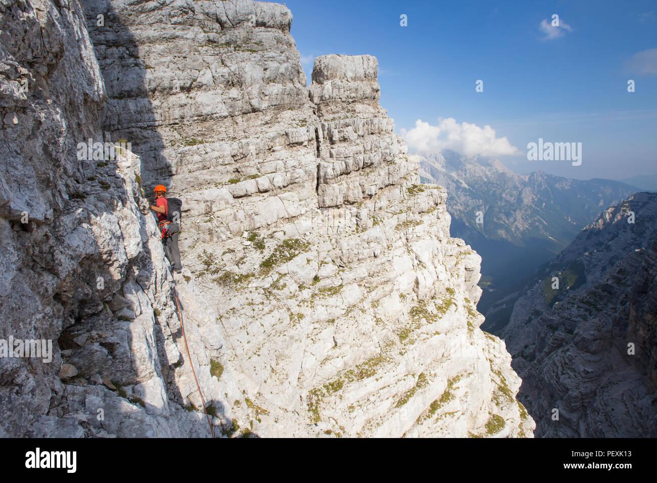 Guía de montaña caminando por el acantilado durante la ascensión de Triglav, en Eslovenia Imagen De Stock