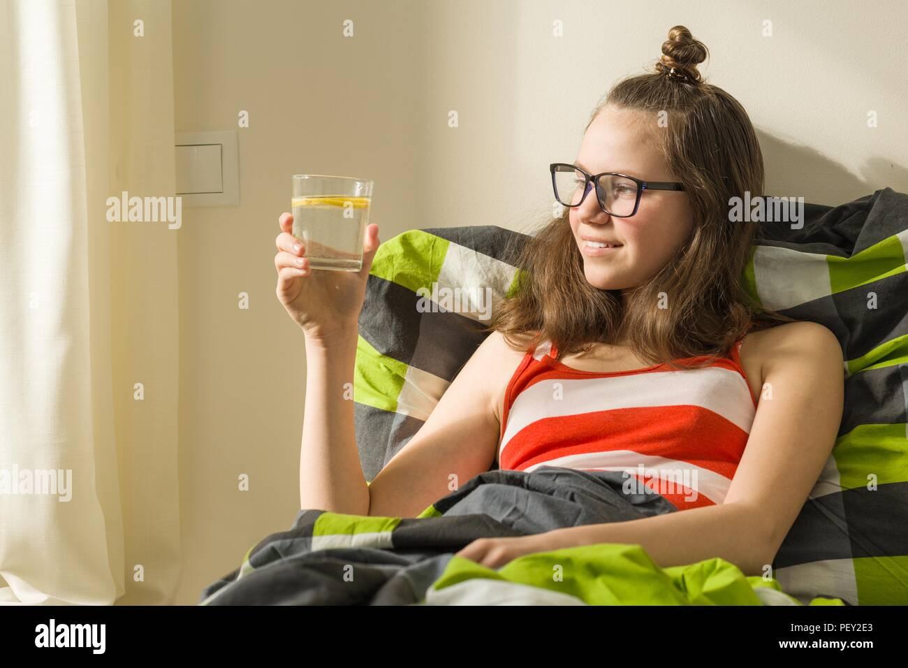 Por la mañana un vaso de agua con limón en las manos de la adolescente. Estilo de vida saludable, dieta, antioxidante Imagen De Stock