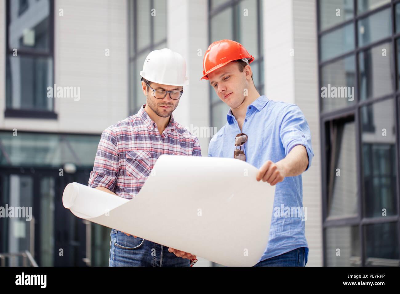 Dos arquitectos están desarrollando un plan de negocios. cerrar foto. Edificio moderno en el fondo de la foto. Imagen De Stock