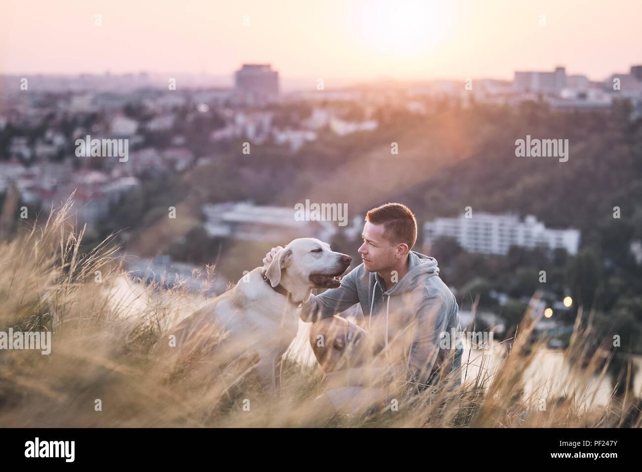 Caminar por la mañana con el perro. Joven y su perro labrador retriever en el prado contra la ciudad al amanecer. Imagen De Stock