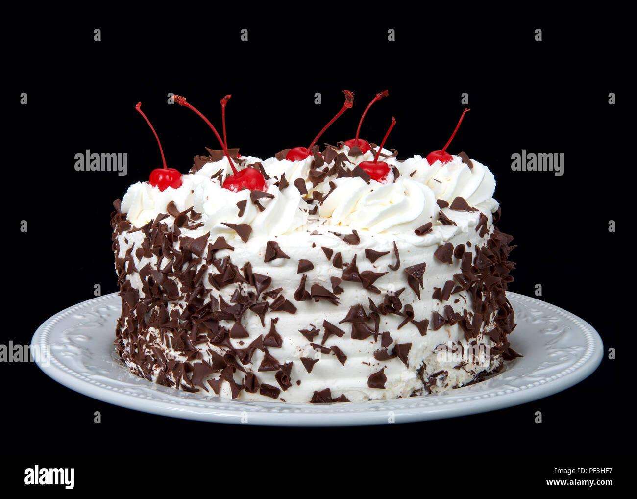 La torta de la selva negra en una placa blanca aislado sobre un fondo oscuro. Crema batida, afeitada dulces de chocolate, cerezas en la parte superior. Foto de stock