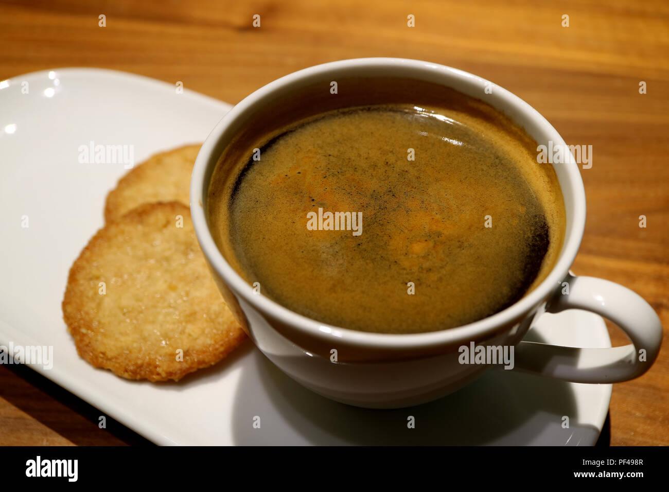 Cerró una taza de café caliente servido con galletas de mantequilla sobre la mesa de madera Imagen De Stock