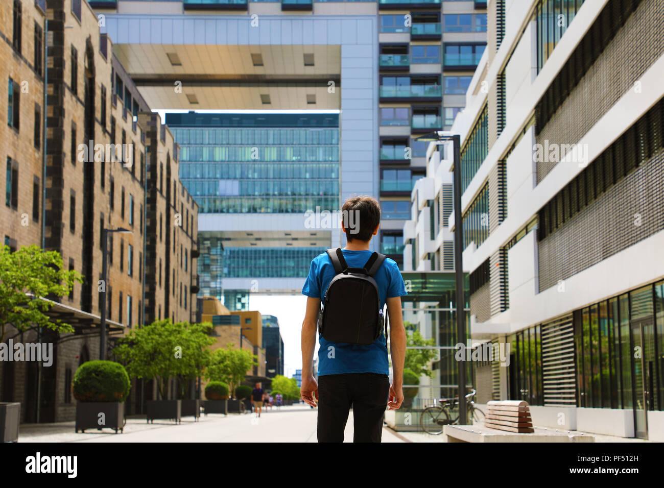 Vista posterior de un hombre joven con mochila recién llegada a la gran ciudad y buscan edificios modernos con perspectivas y oportunidades, Colonia ciudad dist Imagen De Stock