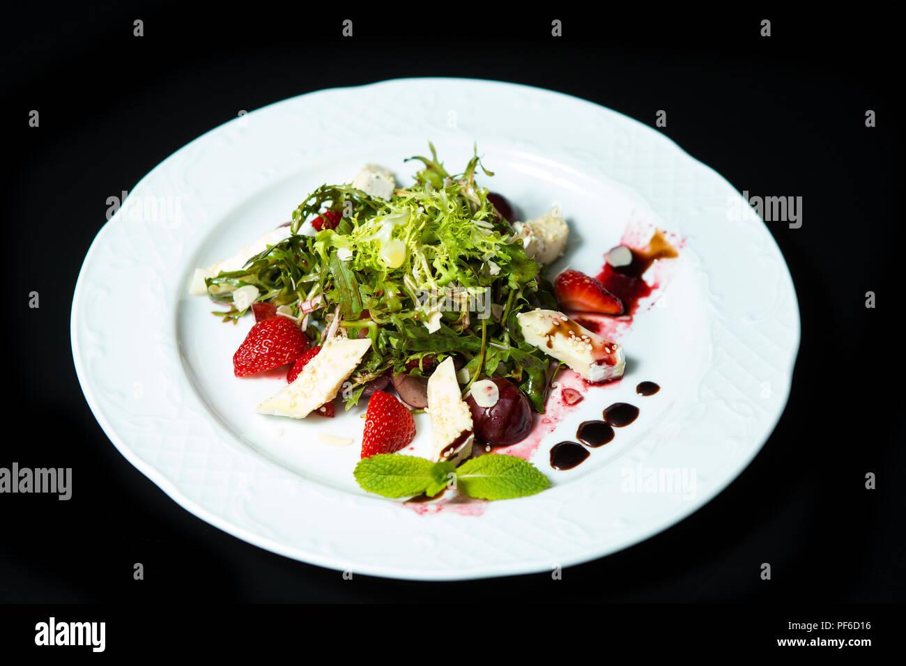Ensalada con cereza, fresa y queso en un plato grande blanca sobre un fondo negro Foto de stock