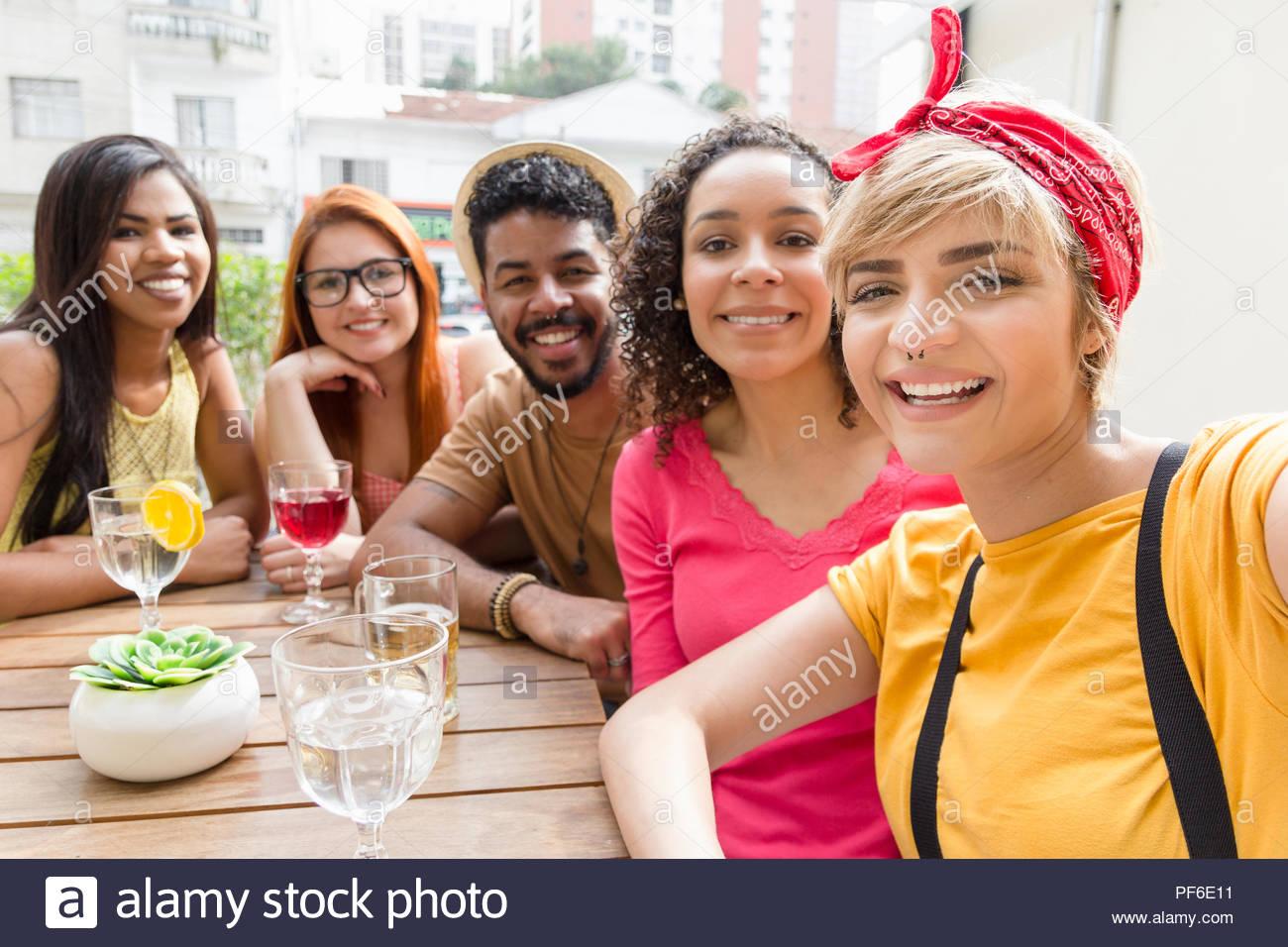 Selfie retrato. Amigos feliz y sonriente sentado en la cafetería al aire libre. Grupo de raza mixta socializar en un partido en el restaurante exterior. Verano caliente, f Imagen De Stock