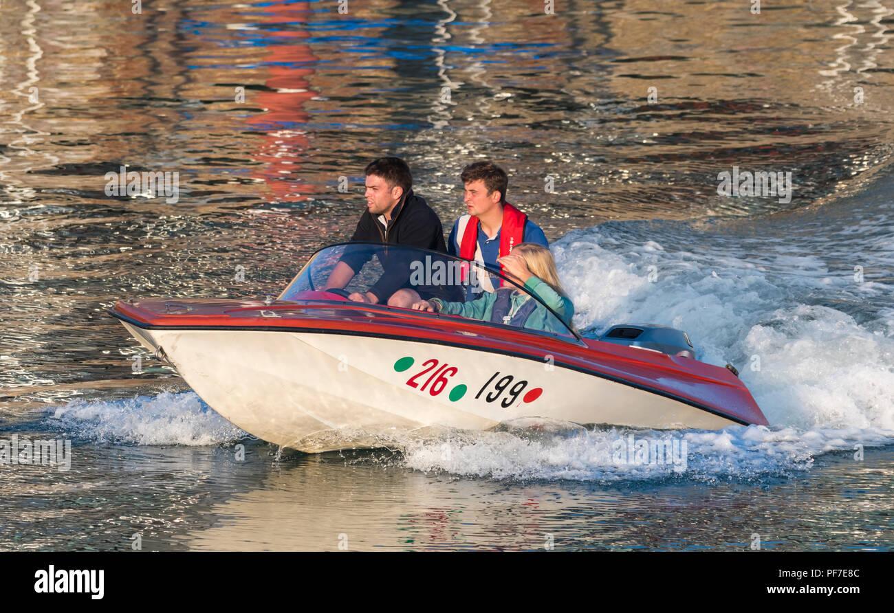 Los jóvenes teniendo una noche viaje en barco por el Río Arun en la hermosa luz del atardecer cuando el sol se pone, en Littlehampton, West Sussex, Inglaterra, Reino Unido. Imagen De Stock