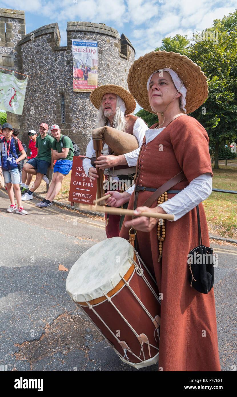 La gente tocando tambores vestidas en trajes de época medieval. Músicos de la calle medieval en Arundel, West Sussex, Inglaterra, Reino Unido. Imagen De Stock