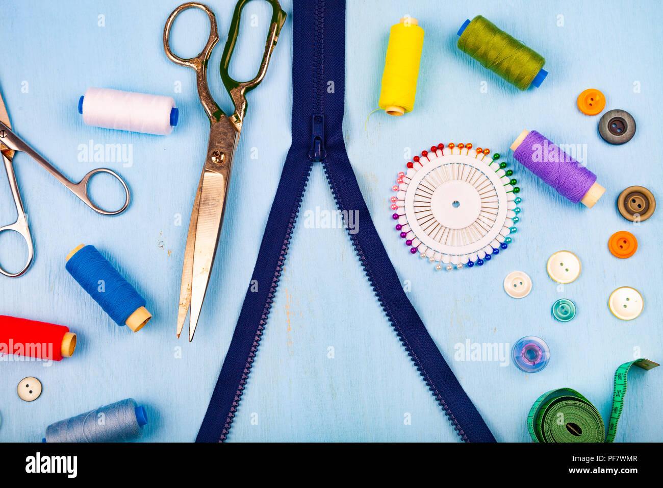 Zipper Unbuttoned y accesorios de costura sobre un fondo de madera azul. Cinta métrica, alfileres, botones, zipper, tijeras e hilo. Foto de stock