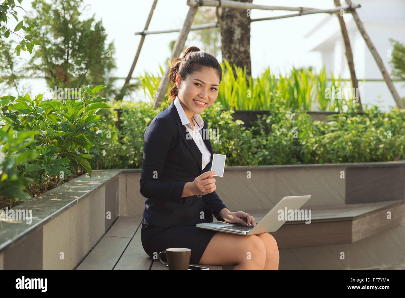 Retrato de mujer de negocios jóvenes feliz celebración y tarjeta de crédito en línea portátil oder, concepto de compras aisladas al aire libre, fuera de fondo. Positiv Imagen De Stock