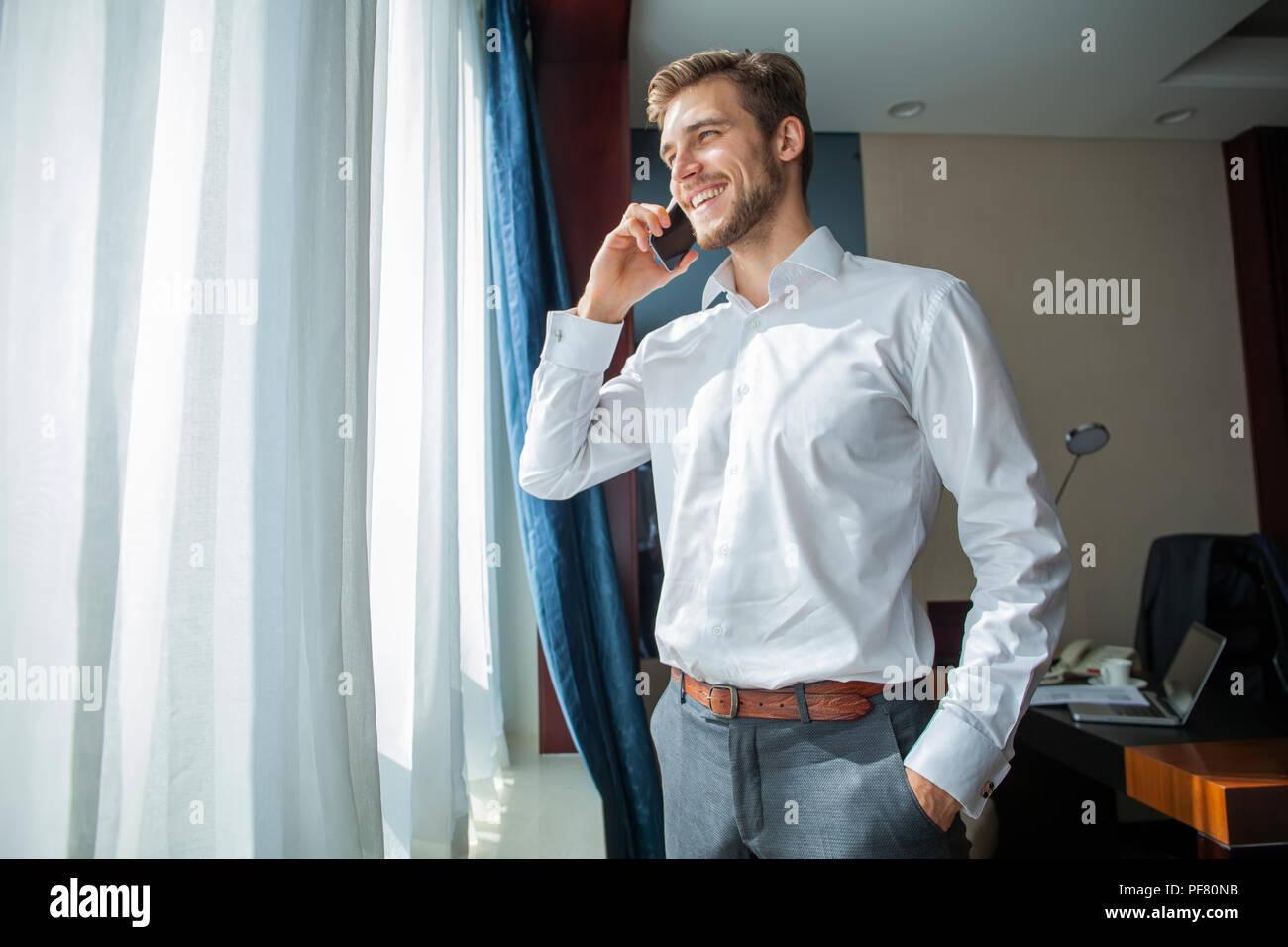 A mediados del Cáucaso adulto empresario hablando con teléfono móvil en la habitación del hotel durante un viaje de negocios. Imagen De Stock
