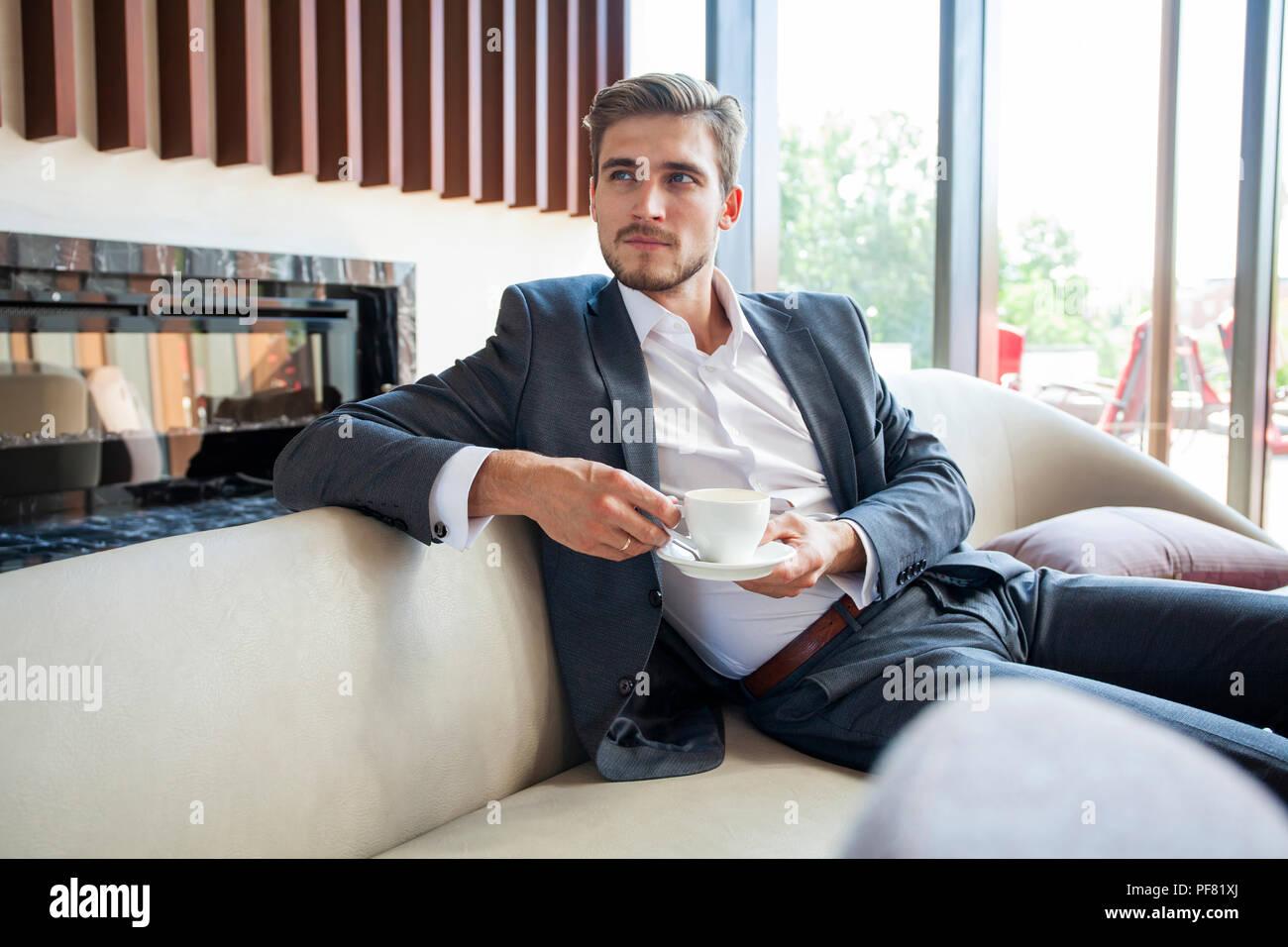 Retrato del joven empresario feliz sentado en un sofá en el vestíbulo del hotel. Imagen De Stock