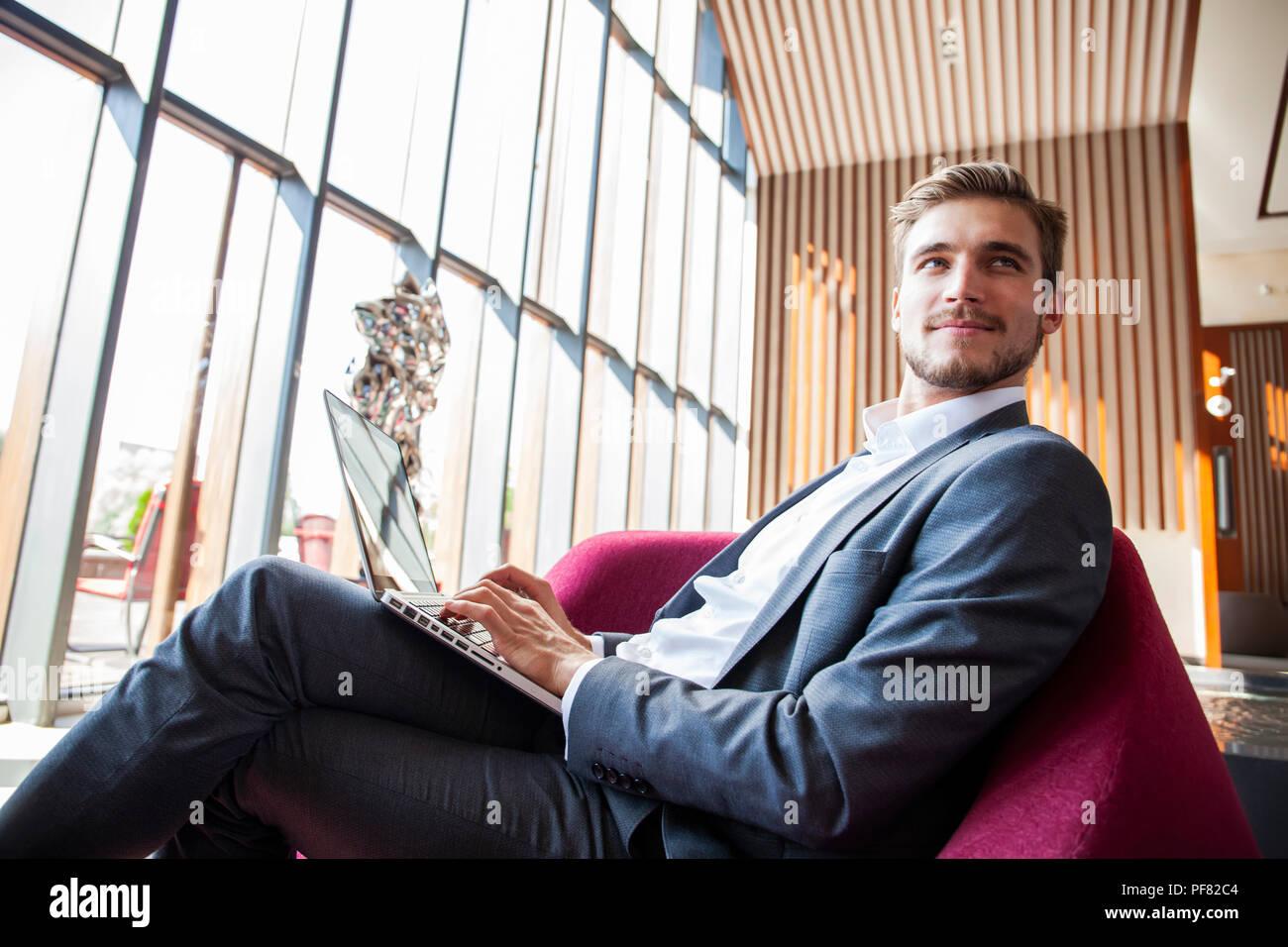 Joven empresario trabajando en el portátil, sentado en el vestíbulo del hotel esperando a alguien. Imagen De Stock