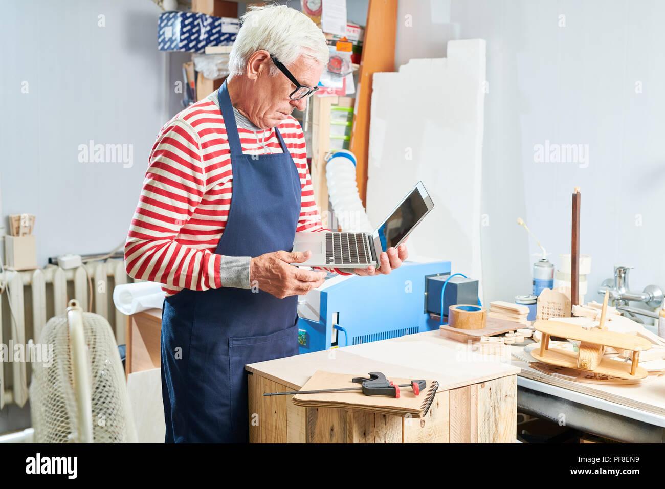 Anciano carpintero con portátil en el taller Imagen De Stock