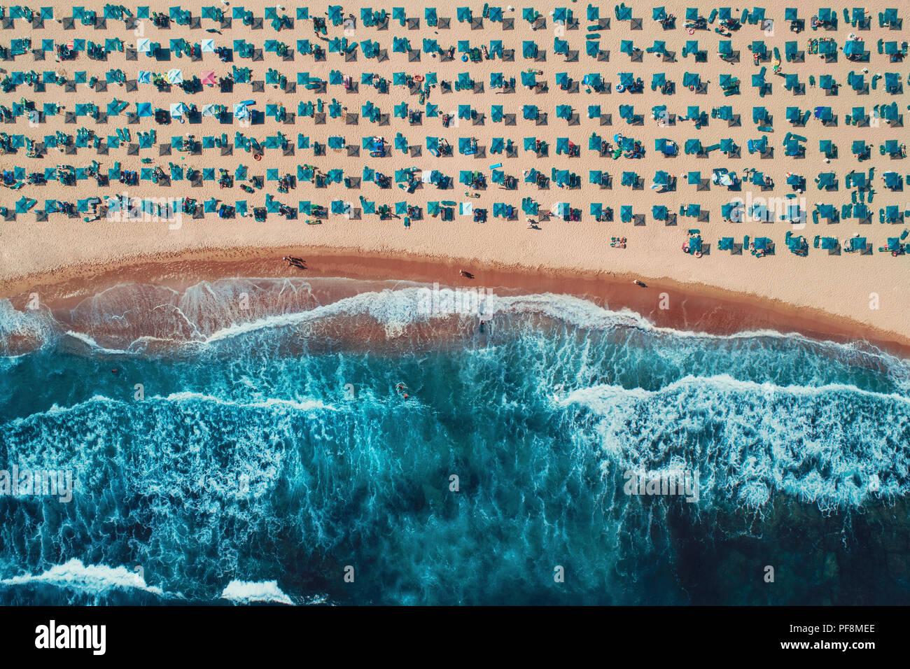 Vista superior de la antena en la playa. Paraguas, la arena y las olas del mar Foto de stock