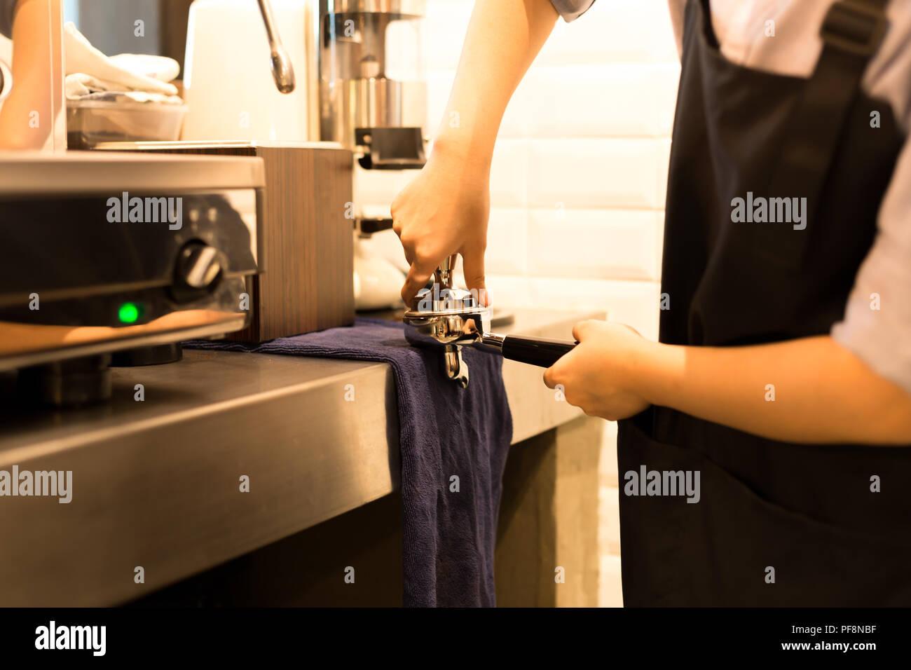 Barista presiona el café molido con tamper Foto de stock