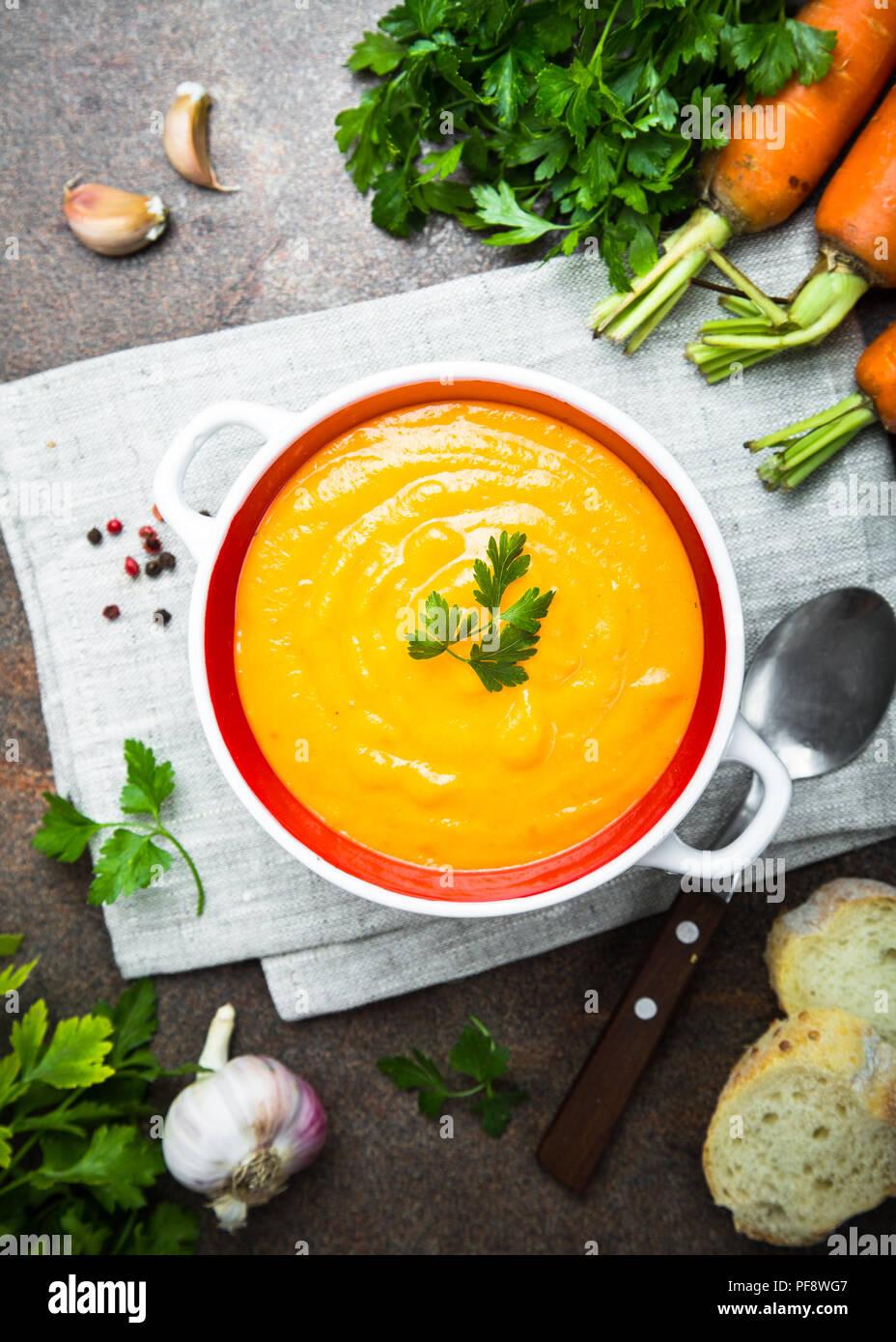 Sopa crema de zanahoria en mesa de piedra oscura. Vegetariana sopa de verduras. Vista desde arriba. Vertical. Imagen De Stock