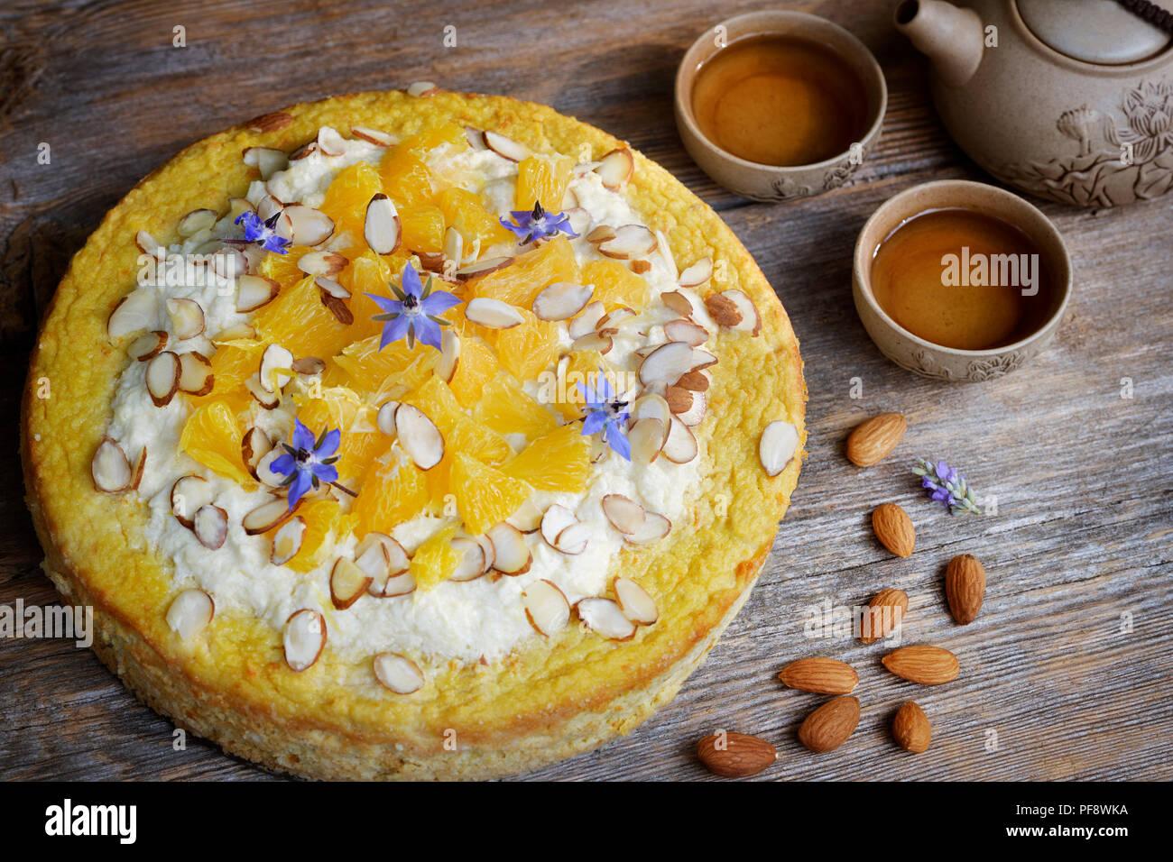 Saludable flourless hecha en casa, sin azúcar de frutas vegano torta de harina de almendras, naranjas y aceite de coco, la comida aún en la vida artística de madera rústica tabl Imagen De Stock