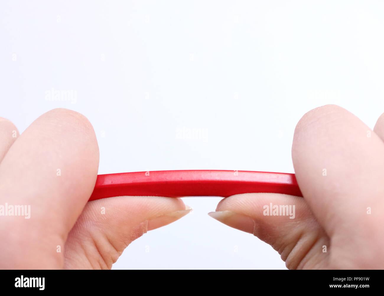 Dos manos sosteniendo un lápiz rojo sobre encaje bajo la presión. Concepto de estrés, manejo de la ira, la presión en el lugar de trabajo, la crianza de los hijos y breakd Imagen De Stock