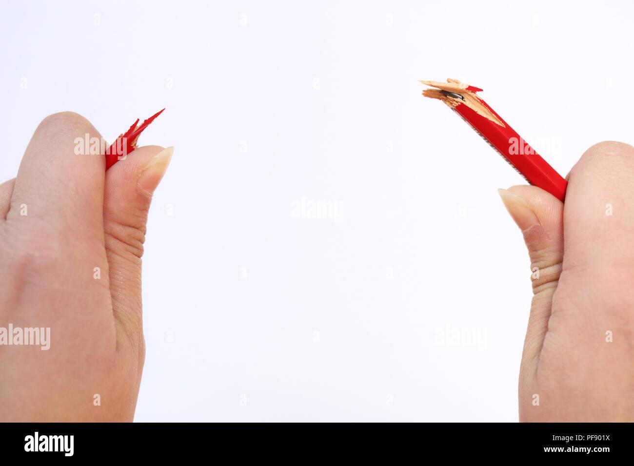 Dos manos sosteniendo un lápiz rojo que acaba roto bajo la presión. Concepto de estrés, manejo de la ira, la presión en el lugar de trabajo, la crianza de los hijos un Imagen De Stock