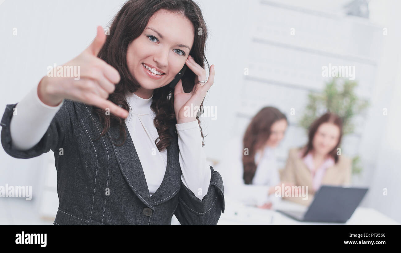 Joven mujer de negocios hablando por teléfono móvil y mostrando el pulgar Imagen De Stock