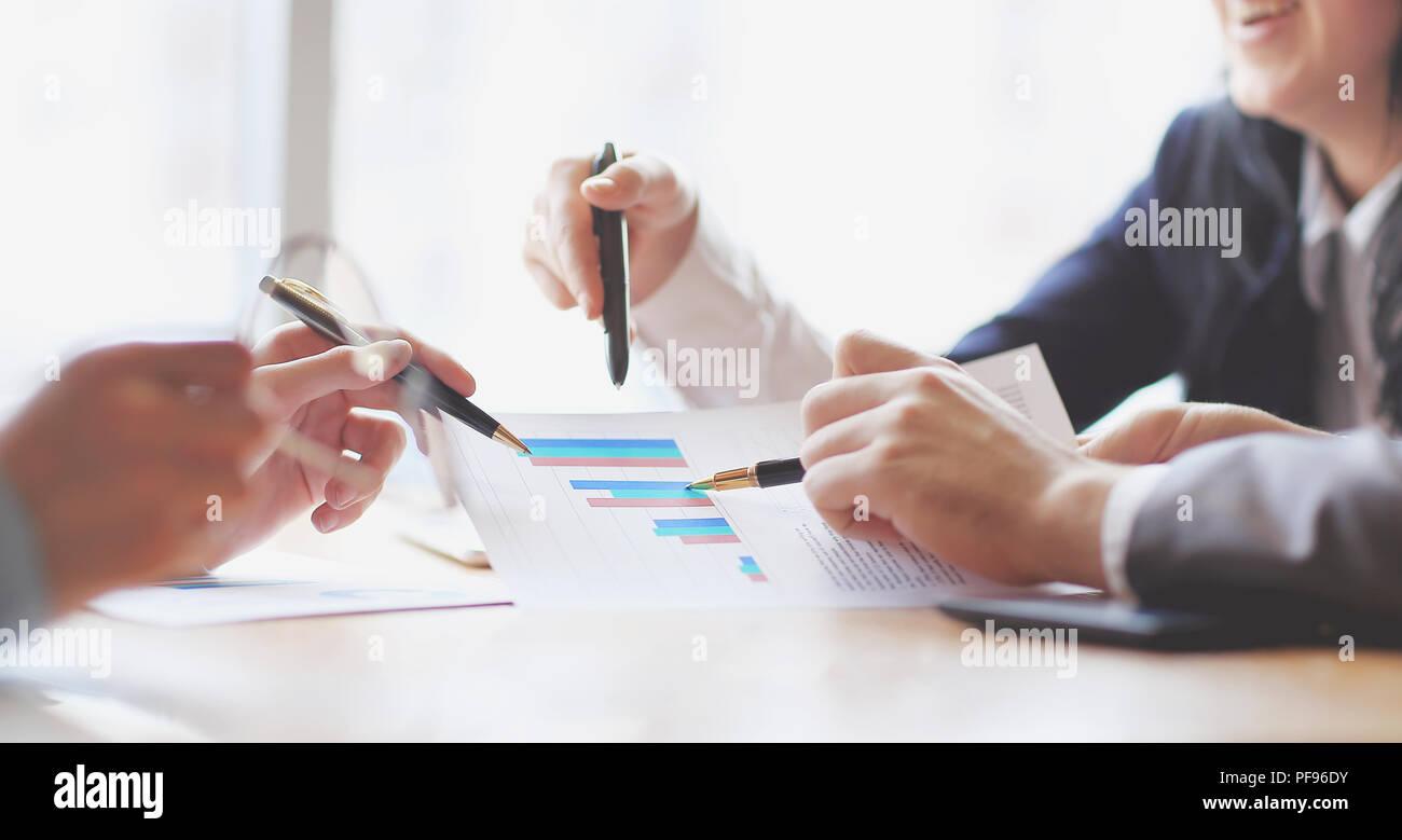 Cerca. El equipo empresarial está discutiendo los beneficios financieros de la compañía Foto de stock
