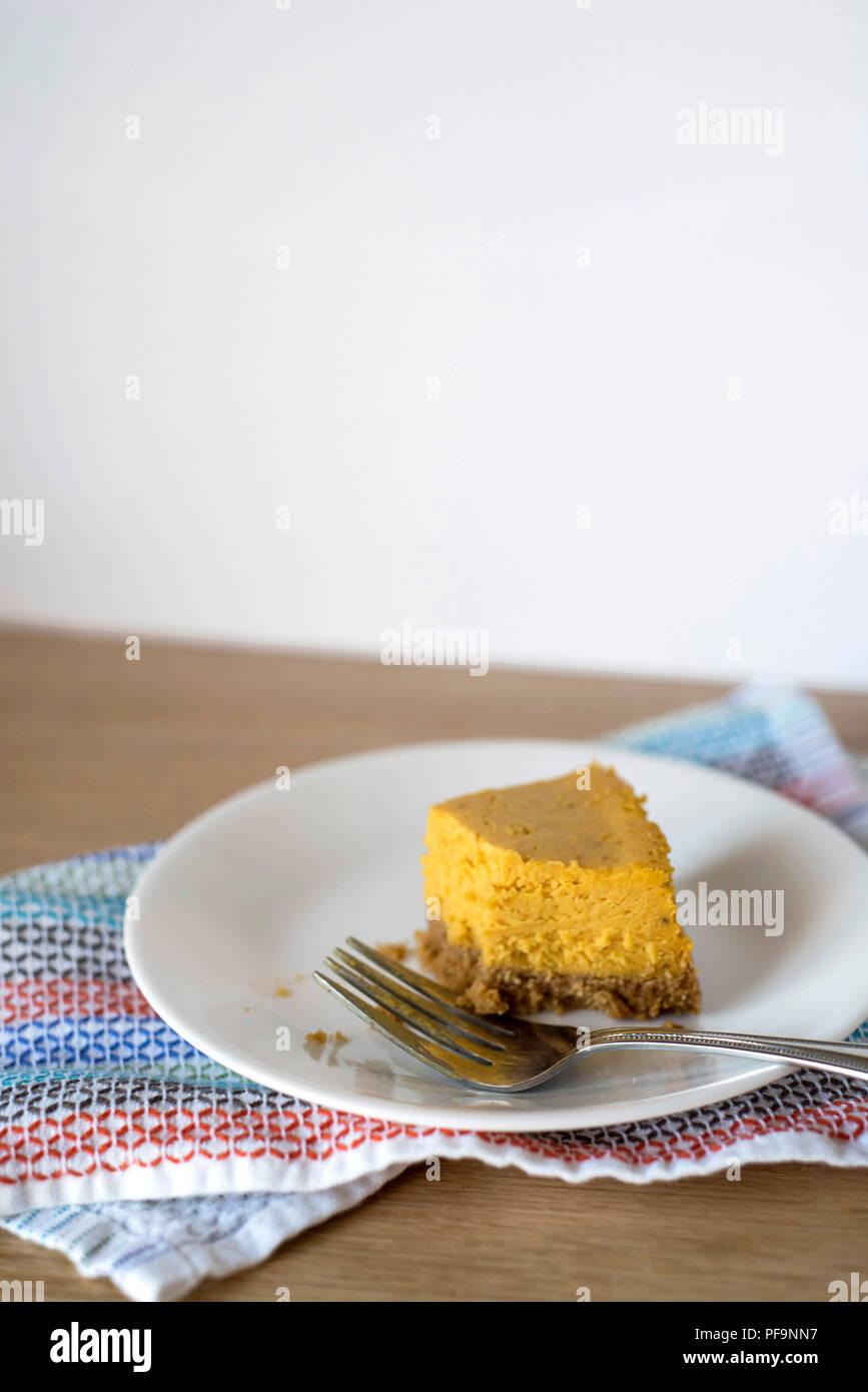 Half-Eaten trozo de tarta de queso y calabaza en un plato con un tenedor Imagen De Stock