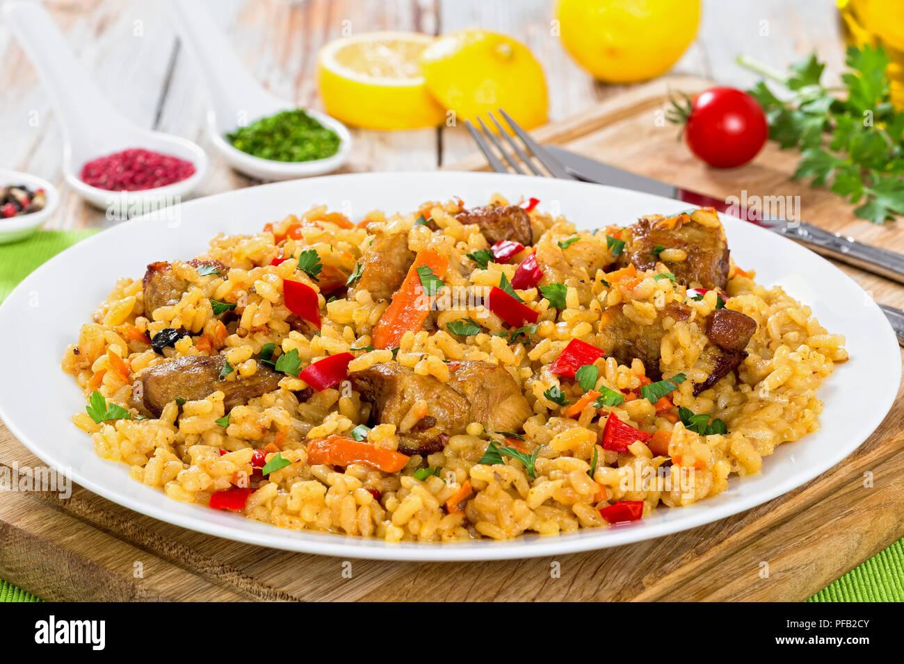 Paella con carne, pimienta, hortalizas y especias en DISH On tabla de cortar, la rodaja de limón, especias y tomates cherry sobre antecedentes, vista desde arriba, clos Foto de stock