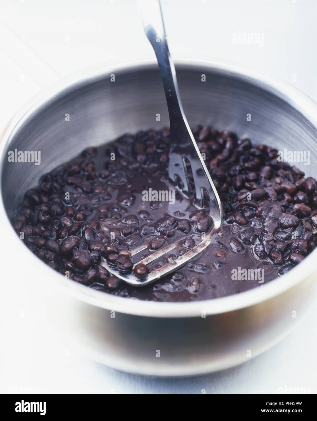Los frijoles negros y el agua en una cacerola grande, se procesan con una patata masher Imagen De Stock