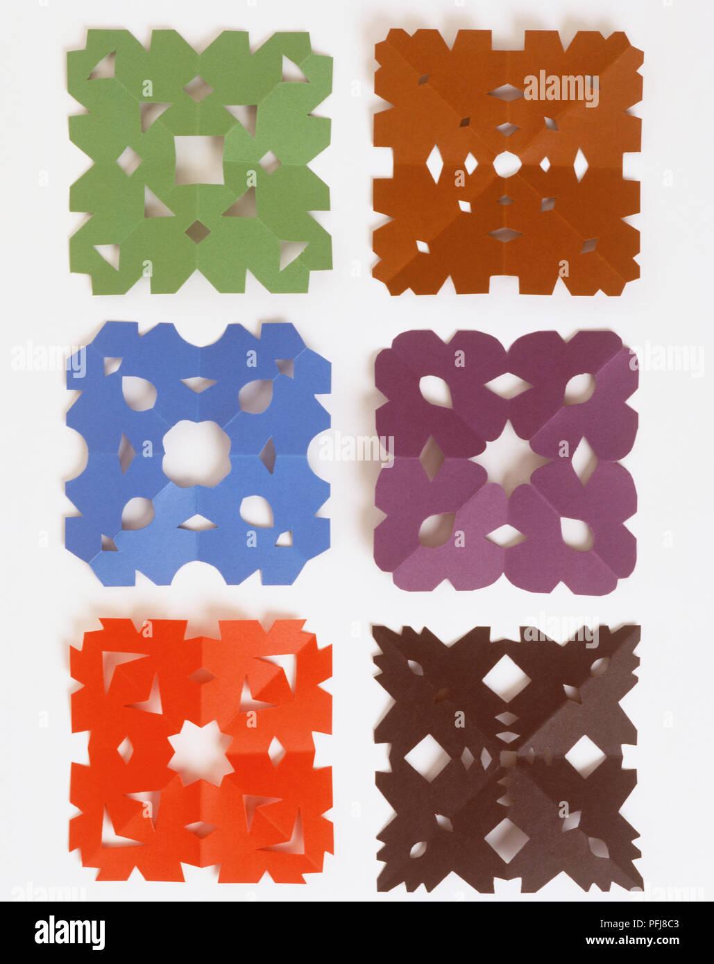 Seis coloridos cuadrados de papel con diferentes patrones cortados en ellos, de cerca. Imagen De Stock