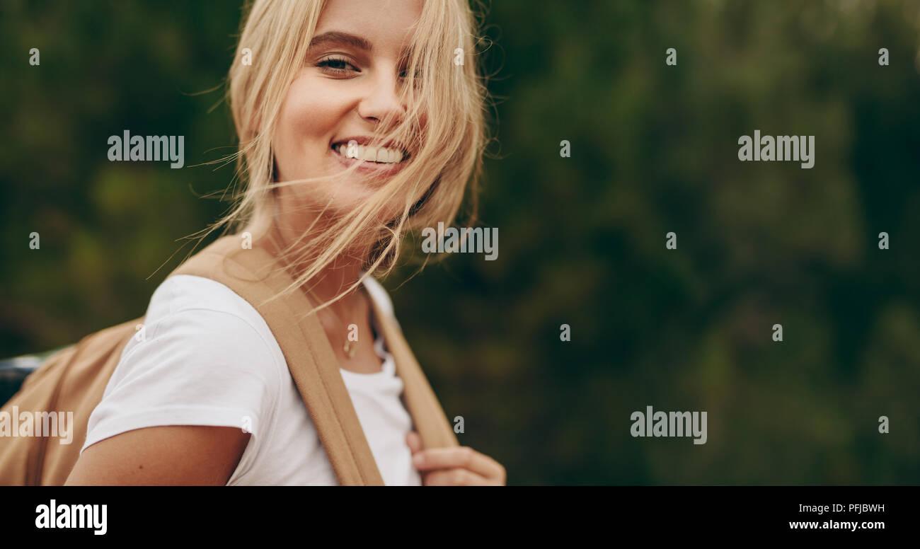 Cerca de la mujer de vacaciones caminando en un parque portando una bolsa. Retrato de una mujer sonriente con pelo marrón volando sobre su rostro. Imagen De Stock