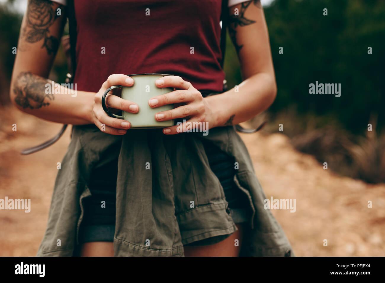 Cerca de la parte media de un viajero mujer sosteniendo el café taza con ambas manos. Mujer de vacaciones caminando a través de un bosque. Imagen De Stock