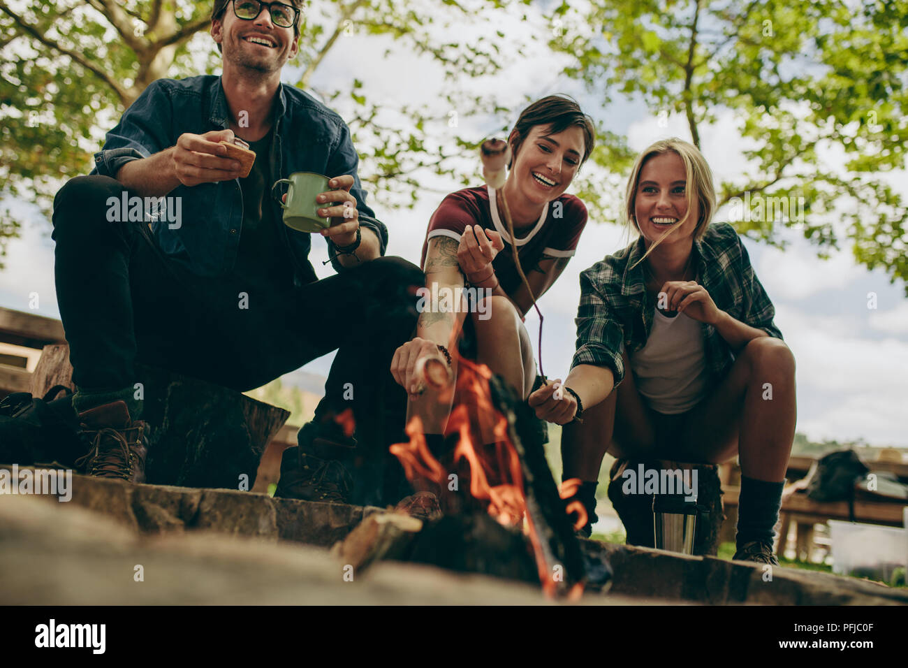 Dos mujeres tostar malvaviscos en la fogata con unos palos mientras un hombre sostiene una taza de café. Amigos sonrientes tostado en alimentos fogata en el campo. Imagen De Stock