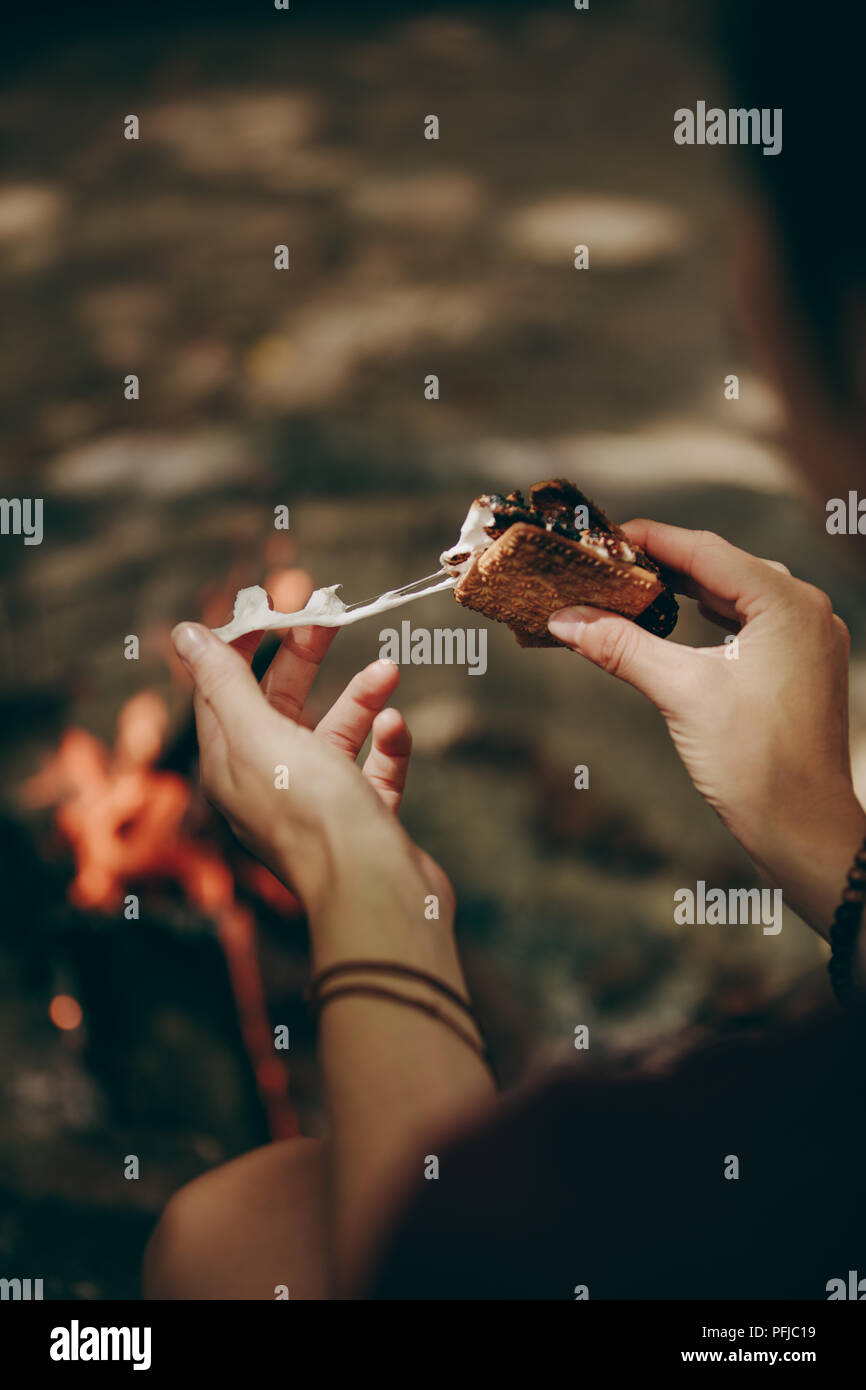 Cerca de mujer sosteniendo un malvavisco galleta sandwich con fogata en el fondo. Persona disfrutando de una comida sentado cerca de la hoguera en un día feriado. Imagen De Stock