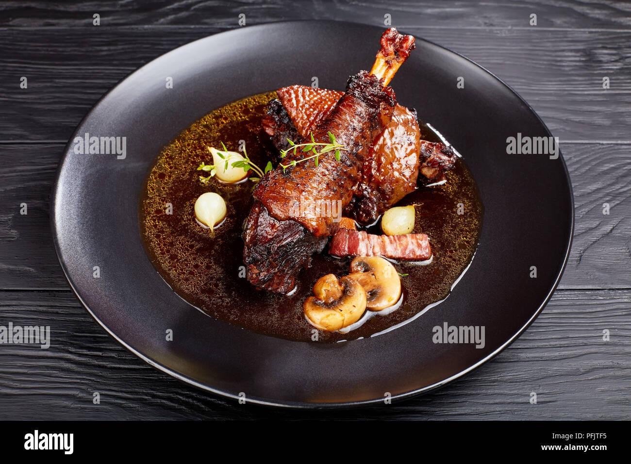 Parte de Sabroso estofado de pollo, muslo y muslo braseado con vino, hierbas, setas y verduras servido en la placa negra, auténtica receta francesa Imagen De Stock