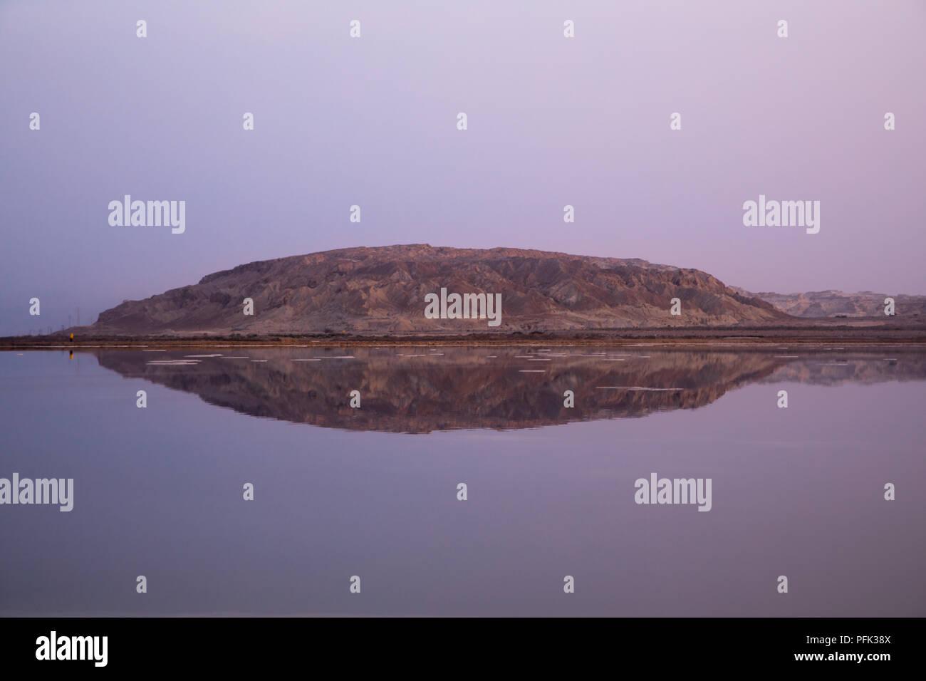 Gran Roca emergiendo del mar Muerto, la tranquila reflexión durante una rosa, Ein Bokek crepuscular, Israel Imagen De Stock