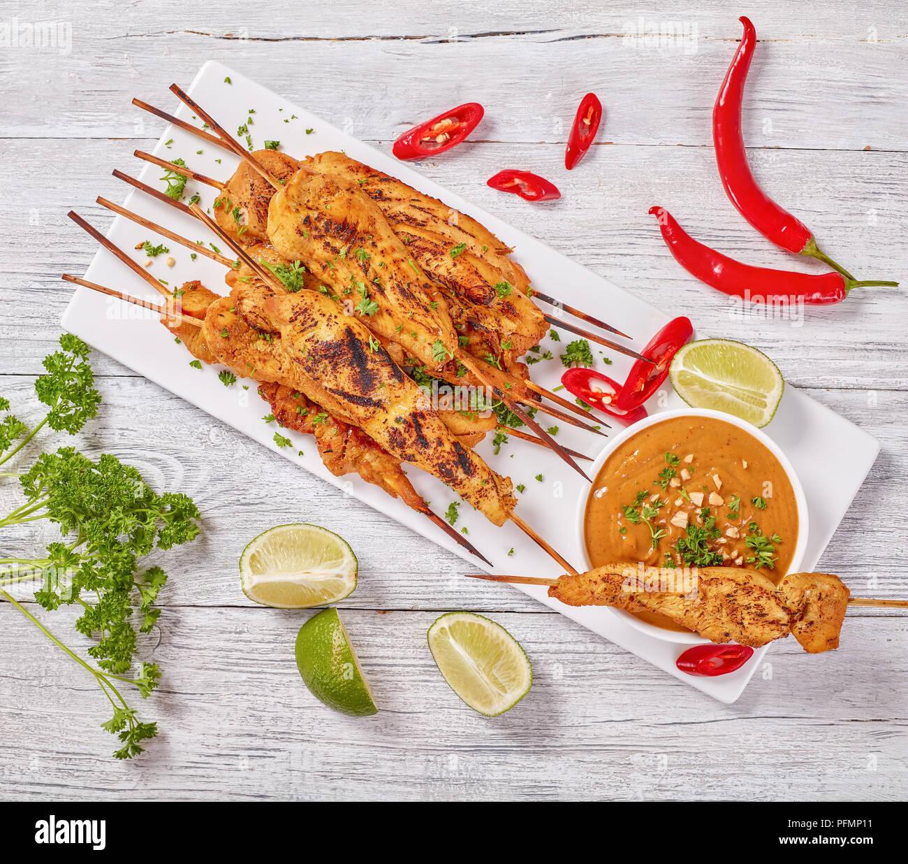 Satay de pollo en brochetas espolvoreado con perejil finamente picado sobre una placa rectangular blanco con salsa de cacahuete. red chili peppers, rodajas de limón y pars Foto de stock