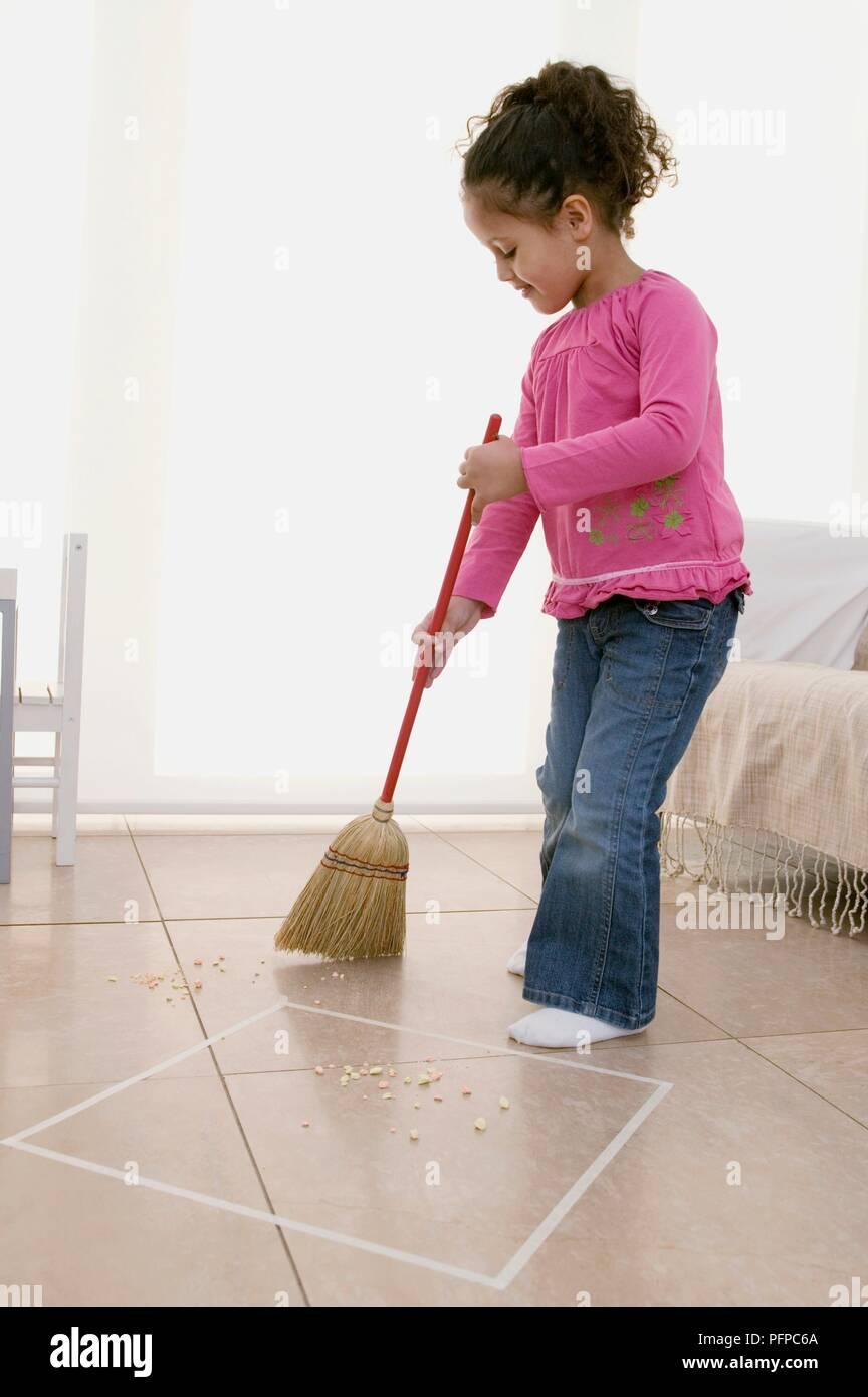 Chica utilizando la escoba para barrer el piso de baldosas for Hormigon encerado sobre suelo de baldosas