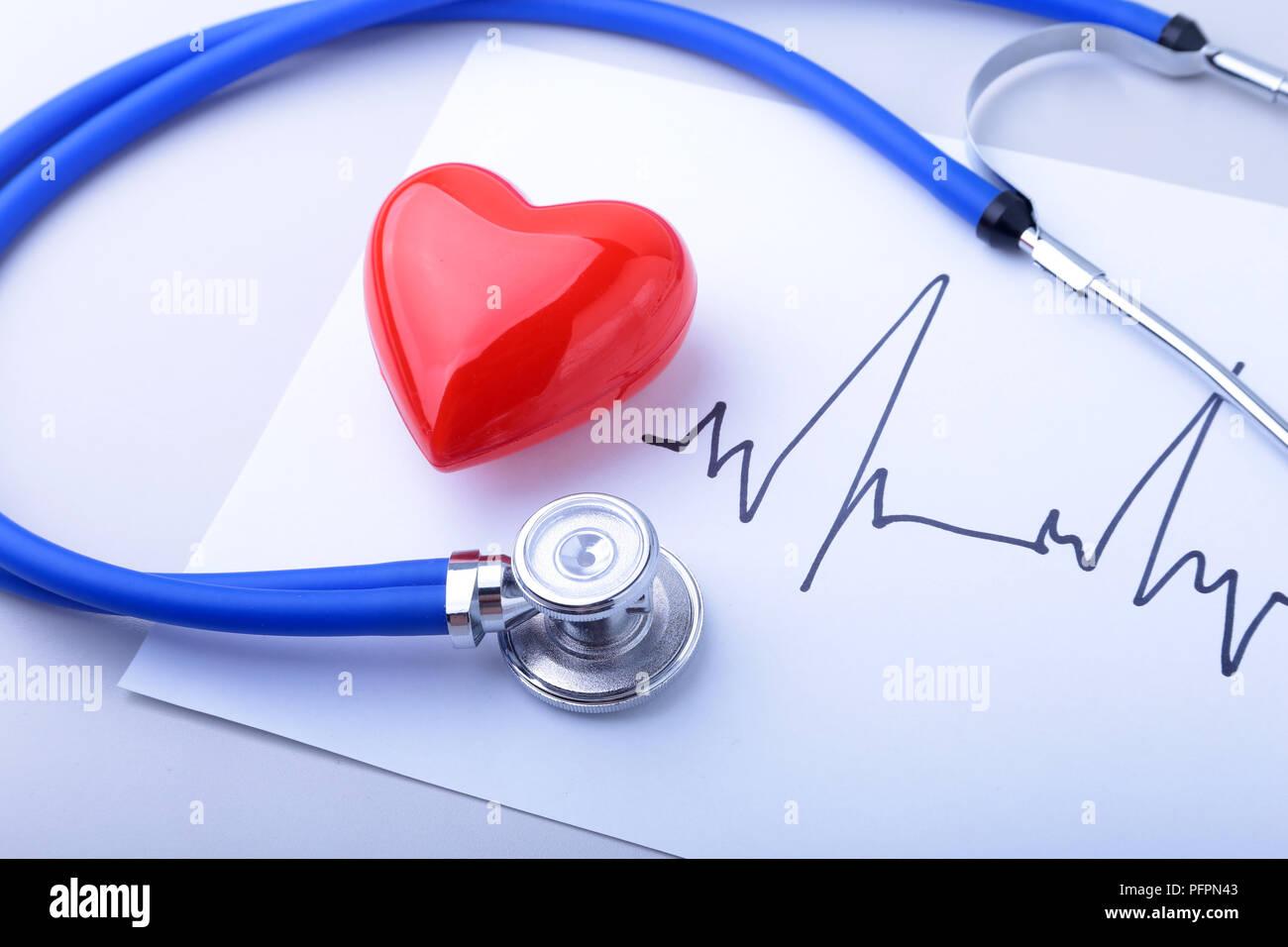 Medical estetoscopio y corazón rojo con electrocardiograma realizado aislado en blanco. La asistencia sanitaria concepto Imagen De Stock