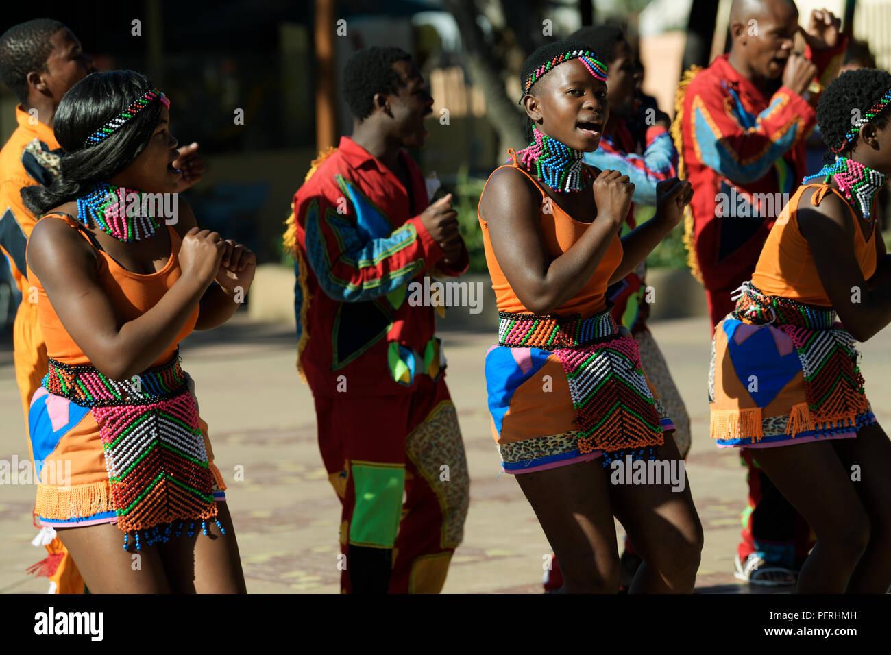 Hombres vestidos de mujer bailando y cantando