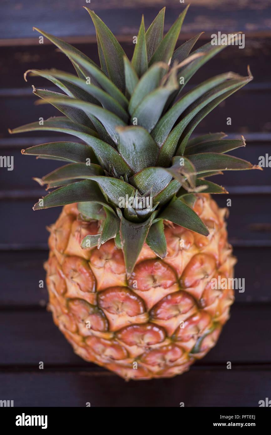 Piña madura, una saludable fruta tropical favorito para su bromelina enzima antioxidante y características establecidas en una mesa de madera con el enfoque selectivo Imagen De Stock