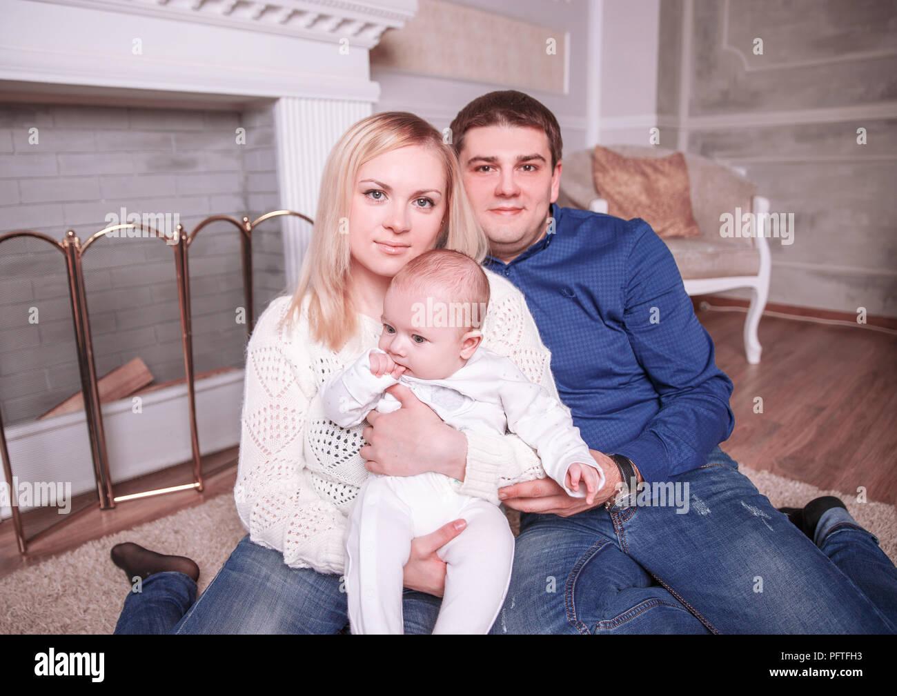 Retrato de una familia feliz: madre, padre y el año de edad en el salón Imagen De Stock