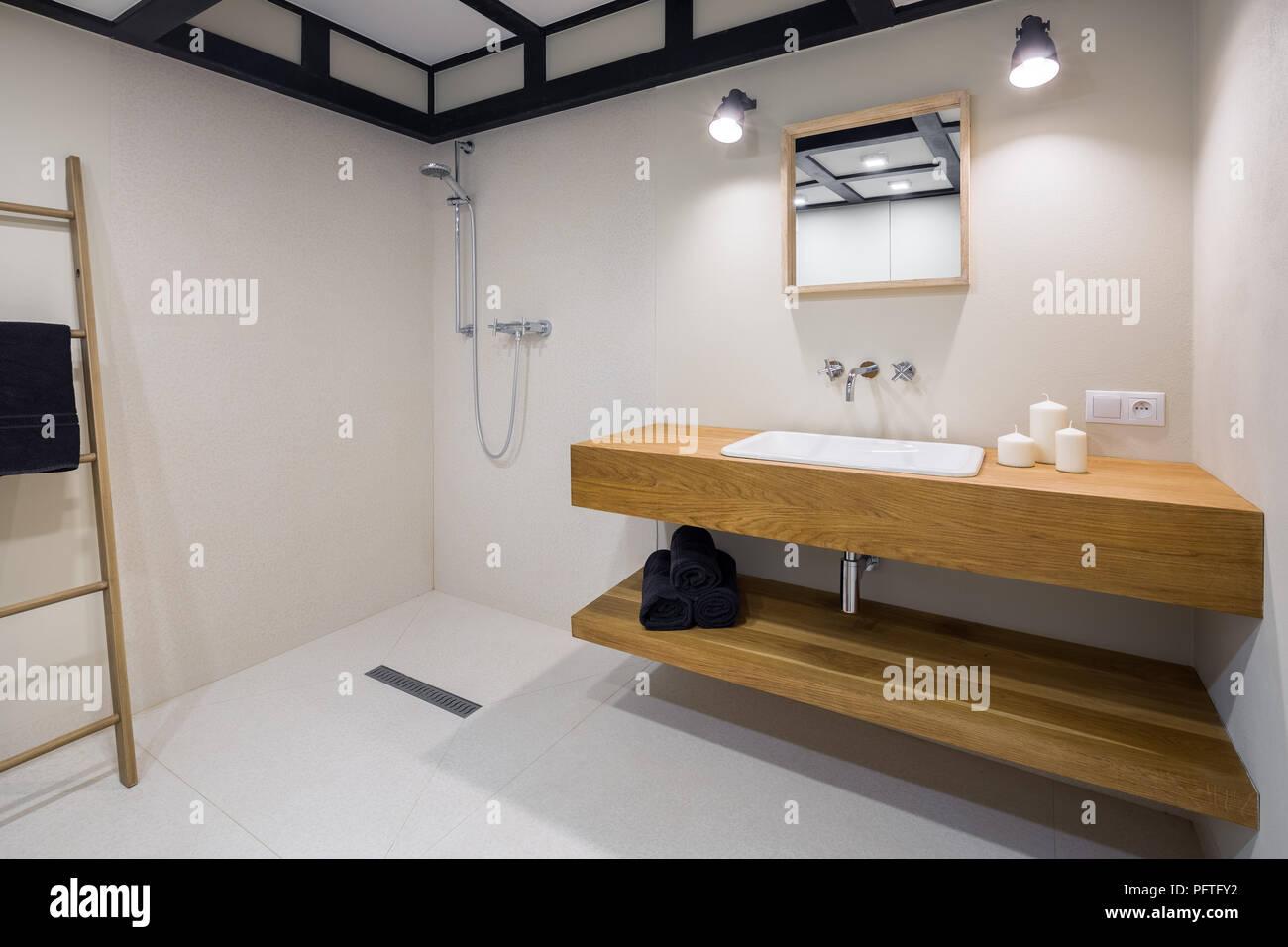 Cuarto de baño minimalista blanco con encimera de madera ...