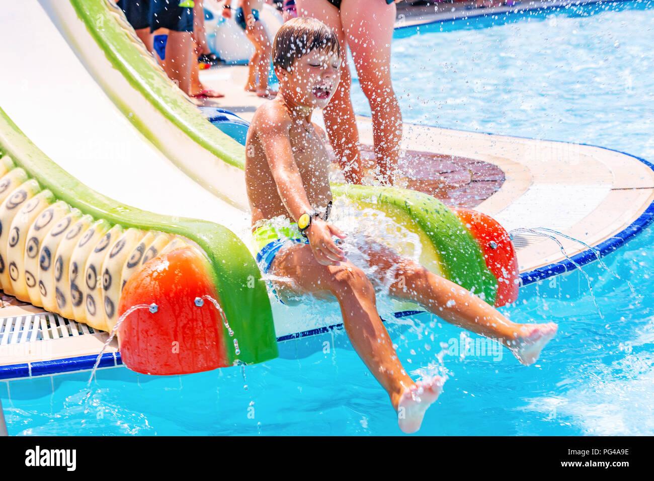 Un muchacho feliz en tobogán de agua en una piscina divertirse durante las vacaciones de verano en un hermoso parque acuático. Un muchacho deslizaba hacia abajo el tobogán de agua y las salpicaduras. Imagen De Stock