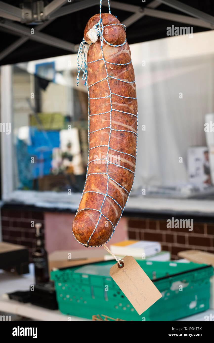 Salchicha grande colgado en un puesto de comida en un mercado callejero británico Imagen De Stock