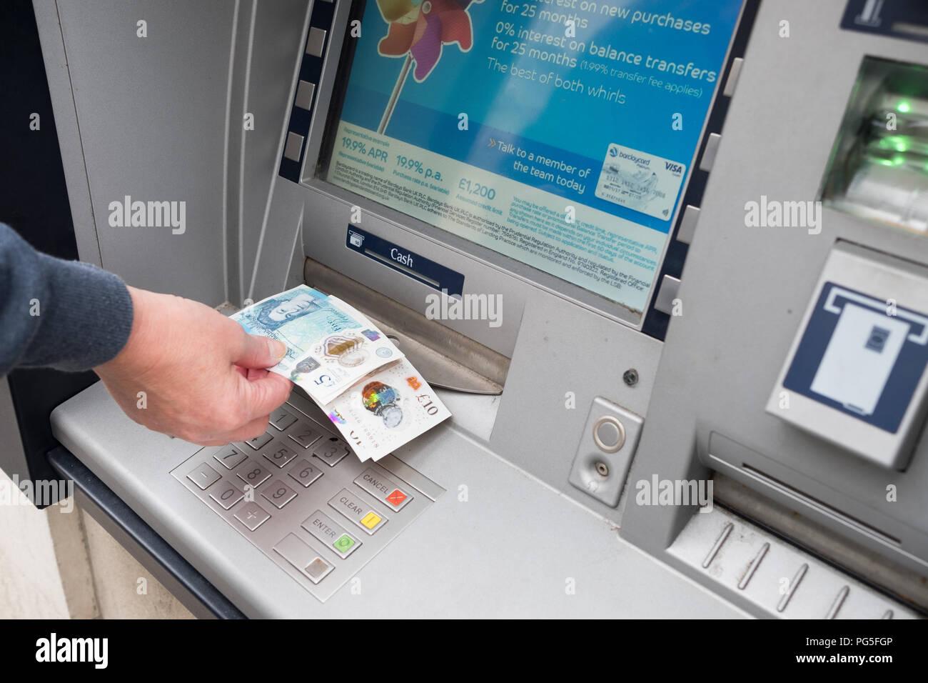 Una mujer quita 5 libras y 10 notas desde un fuera de Barclays Bank, el agujero en la pared, máquina de cajero automático Foto de stock