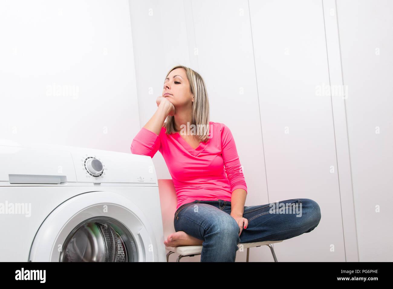 8a029fd94 Los quehaceres domésticos: joven lavando ropa - esperando el programa de  lavado a fin, impaciente por tener su ropa lavada, seca y lista para usar  ...