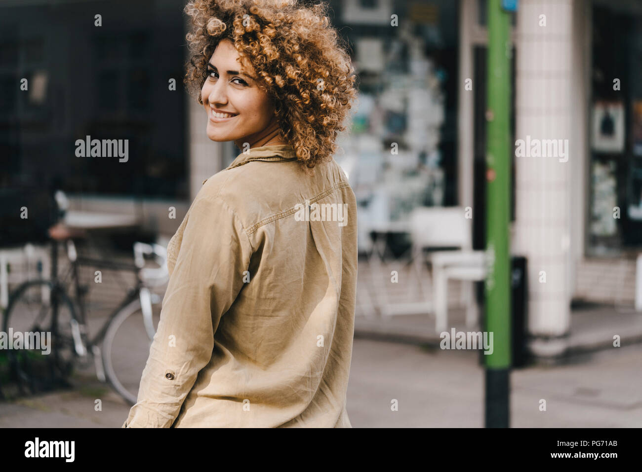 Mujer en la ciudad, caminando, sonriendo Imagen De Stock
